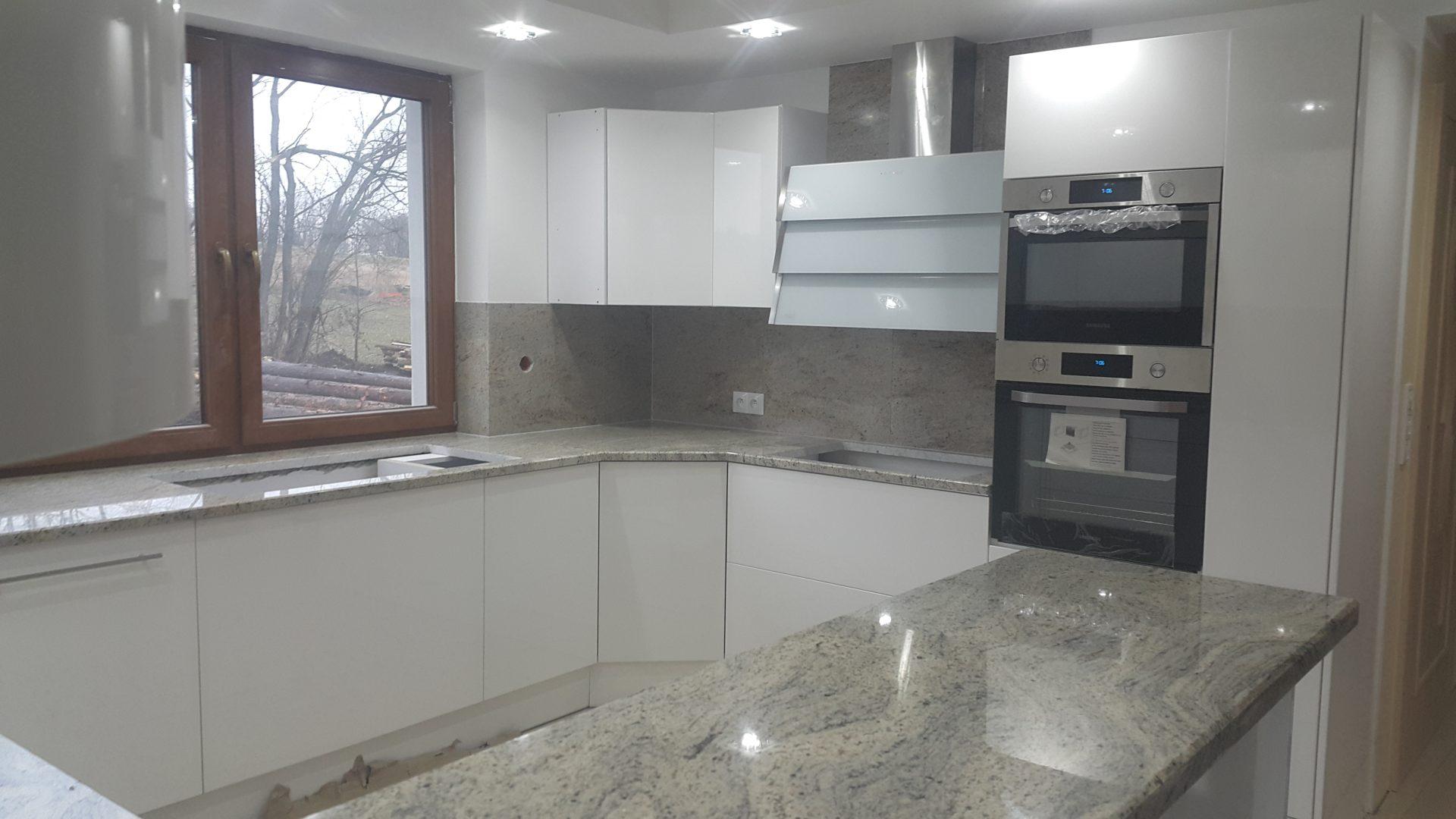 Aranżacja białej kuchni w połączeniu z szarym, granitowym blatem kuchennym