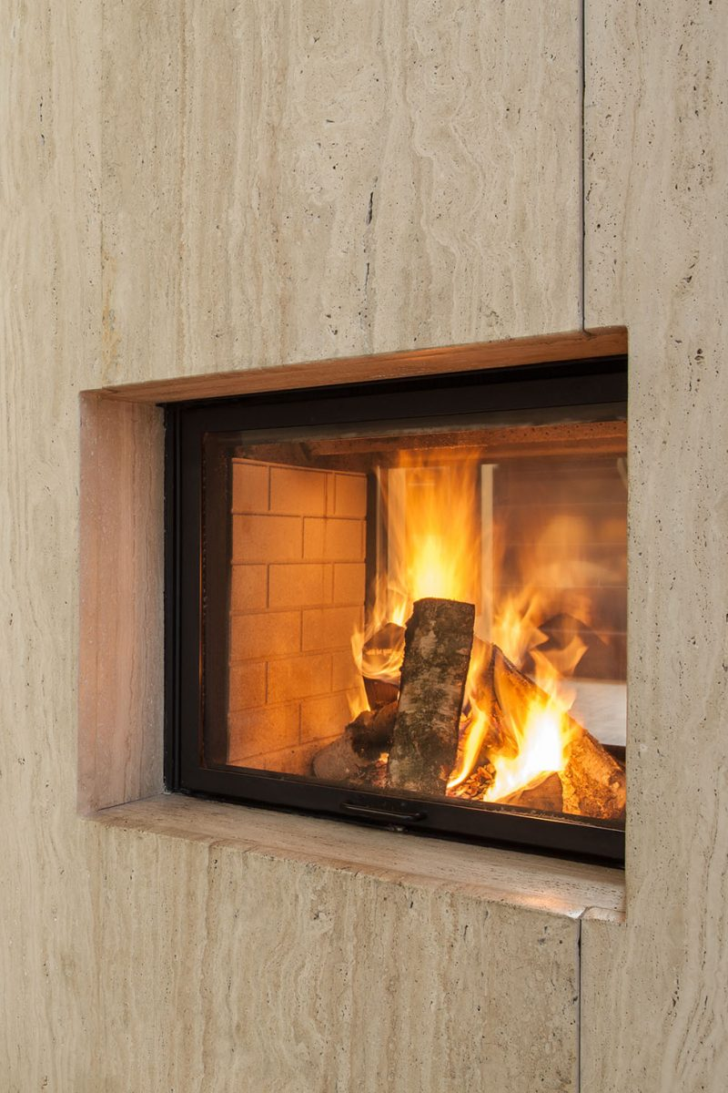 Travertine house: Burning fireplace and pieces of wood